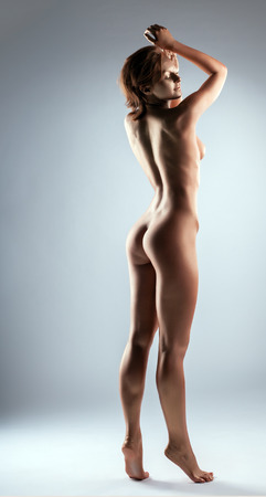 naked statue: Smiling skinny bronzed woman posing in studio, on gray background Stock Photo