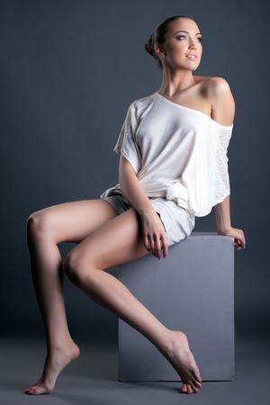leggy girl: Image of beautiful leggy girl sitting on cube in studio