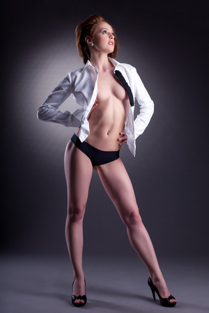 Leggy slim model posing in unbuttoned white blouse, on gray background photo