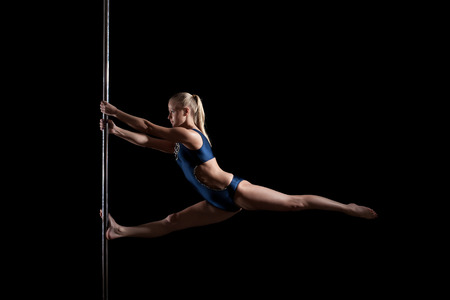 Pretty young blonde dancing on pylon, isolated over black background