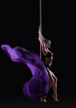 pole dance: Giovane ballerina polo sottile che propone con un panno viola, isolato su fondo nero