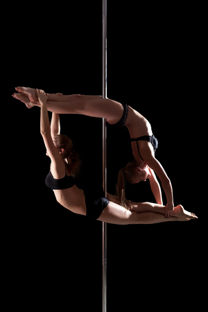 female stripper: Duet of flexible young pole dancers, isolated on black