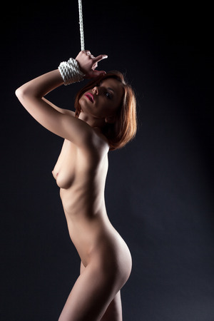 Beautiful red-haired wrapped woman posing naked in studio photo