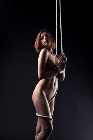 Image of sexual naked woman entwined rope in studio photo