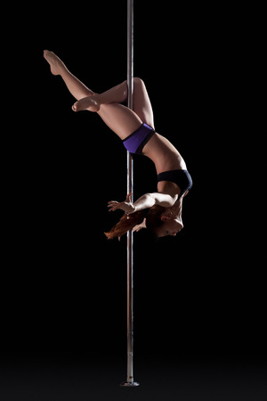 stripper pole: Athletic young pole dancer, isolated on black background