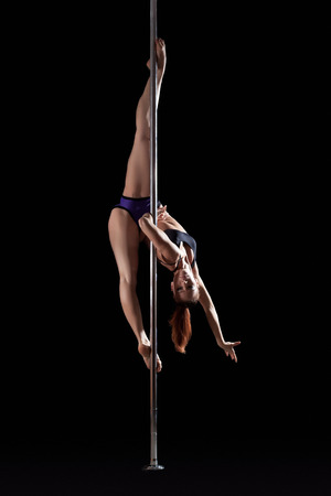 female stripper: Young flexible woman dancing on pylon, isolated over black background Stock Photo