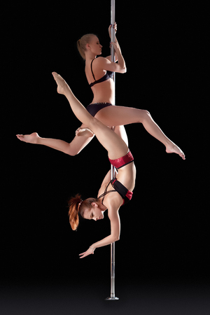 stripper pole: Two athletic young girls dancing on pilon, isolated over black