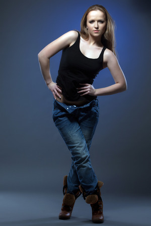 Slender young model shows trendy casual clothes in studio photo