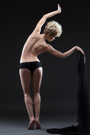 Rear view of flexible young woman dancing topless with cloth photo