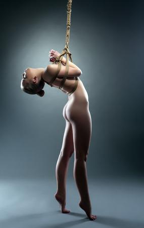Studio shot of flexible nude girl hanging on rope in studio