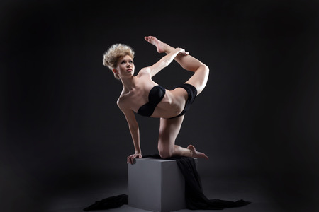 Studio shot of graceful young model dancing on cube photo