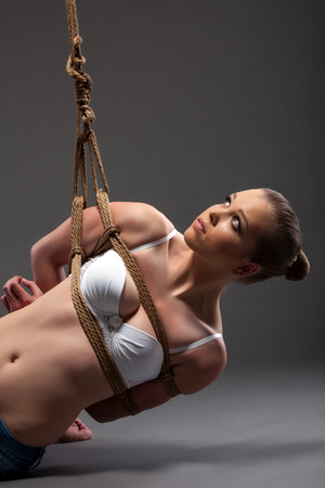 Image of pretty young woman hanging on rope in studio photo