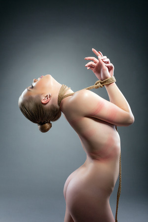 Image of naked girl with rope around her neck and hands photo