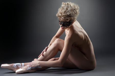 Curly blonde posing nude in carnival mask and pointes photo
