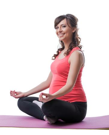 pregnant woman yoga: Smiling pretty pregnant woman meditating in studio, close-up Stock Photo