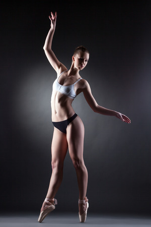 Shot of slim graceful ballerina posing in lingerie, on gray background photo
