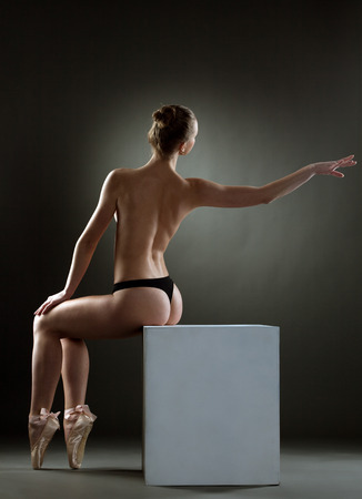 Graceful topless girl posing sitting on cube in studio photo