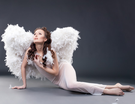 Beautiful sad woman posing in angel costume, on gray background photo