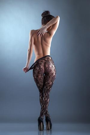 Imagen de la mujer desnuda delgada posando en medias, de vuelta a la cámara Foto de archivo