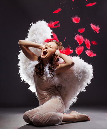 Attractive woman dressed as angel cries in studio, on gray background Stock Photo
