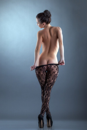 Slim nude woman takes off her tights, back to camera photo