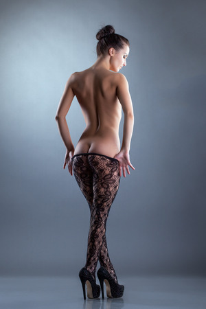 Beautiful nude woman posing in translucent tights, back to camera photo