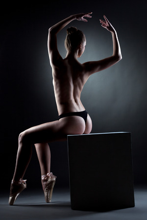 Rear view of muscular topless dancer sitting on cube photo