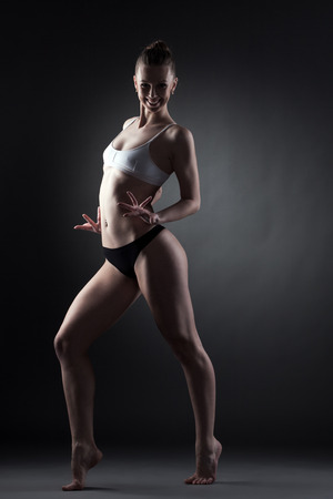 Merry contemporary dancer posing looking at camera, on gray background photo