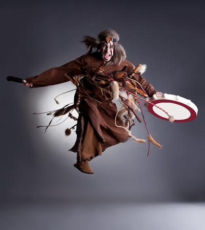 barbarian: Studio shot of angry shaman posing in jump, on gray background