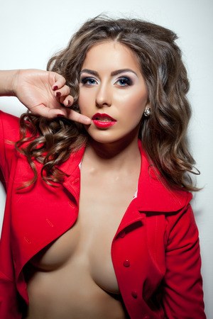 Portrait of hot curly brunette posing topless in red jacket photo