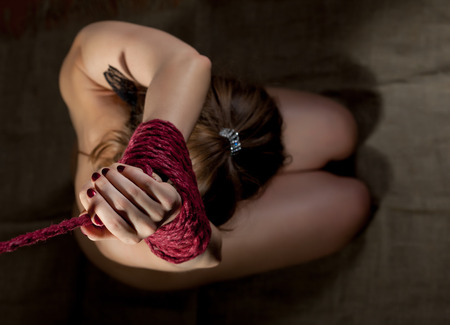 Top view of womans hands bound with red rope, close-up