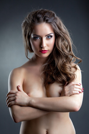 Confident brunette posing naked in studio, her arms crossed