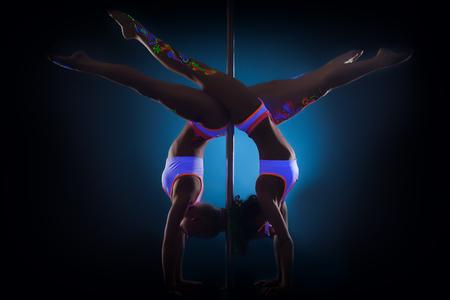 Image of slender pole dancers posing standing on hands