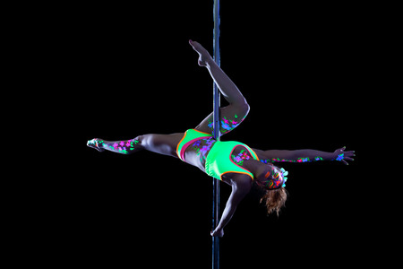 Lovely girl with luminous makeup dancing on pole, isolated over black background photo