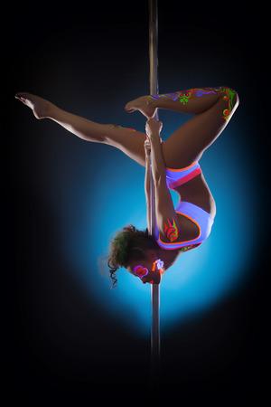 Schot van aantrekkelijke go-go danser poseren op pyloon Stockfoto