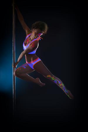 dancers: Image of sexy slim pole dancer posing in jump