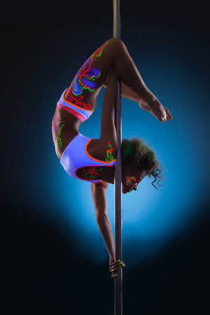 Image of slender young woman dancing on pole