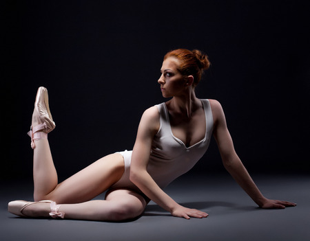 Fascinating red-haired ballerina posing in studio, on gray background photo