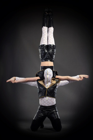 boy gymnast: Shot of acrobatic stunt performed by go-go dancers, on gray background