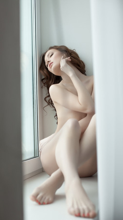 Languid nude model posing lying on windowsill in hotel photo