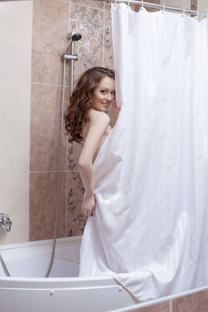Shy smiling woman posing nude in hotels shower photo