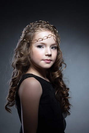child model: Adorable girl posing with gold decoration on her head Stock Photo