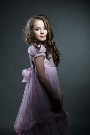 niño modelo: Niña adorable que presenta en elegante vestido de color rosa, sobre fondo gris Foto de archivo