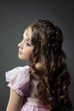 niño modelo: pequeña fashionista linda que presenta de nuevo a la cámara, primer plano