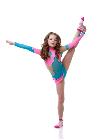 Beautiful little gymnast exercising in studio, isolated on white