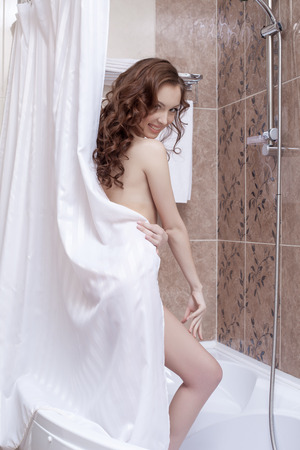 Image of smiling nude model posing in shower, close-up photo