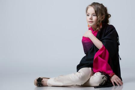niño modelo: Adorable niña de moda en estudio, sobre fondo gris