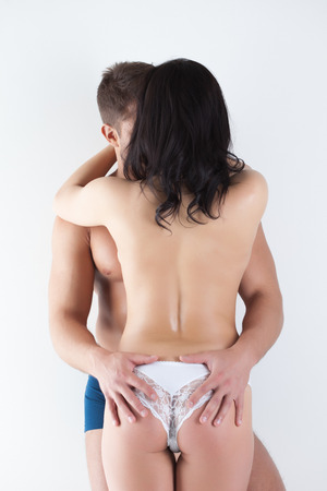 Rear view of young lovers embracing in studio photo