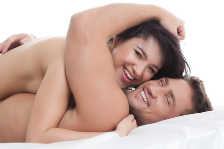 Happy naked lovers embracing lying in bed, close-up photo