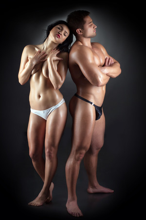 Studio shot of sensual young athletic sex partners, on gray background photo